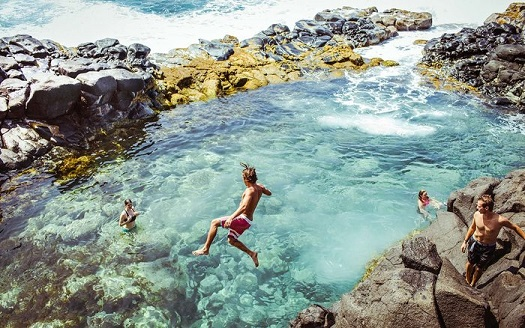 Friends having fun in Queen's Bath, Kauai, Kauai County, Hawaii, USA
